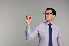 Handsome businessman in shirt,tie, glasses holding pen. Writ. Confident successful young handsome man businessman in shirt, tie, glasses holding pen on grey Stock Photo