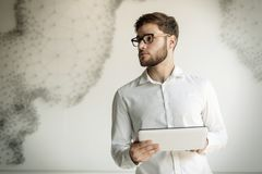 Businessman wearing glasses using tablet. Handsome businessman in shirt wearing glasses using tablet pc Royalty Free Stock Photo