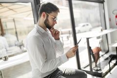Businessman wearing glasses using tablet. Handsome businessman in shirt wearing glasses using tablet pc Stock Photography