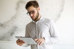 Businessman wearing glasses using tablet Royalty Free Stock Images