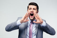Handsome businessman shouting over gray background Stock Images