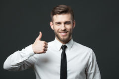 Handsome businessman showing thumbs up sign on dark gray backgro Royalty Free Stock Photos