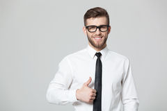 Handsome businessman showing thumbs up sign on gray background. Royalty Free Stock Photo