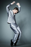 Handsome businessman in silver suit dancing. Stock Images