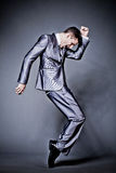 Handsome businessman in silver suit dancing. Royalty Free Stock Photography