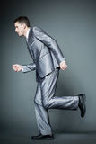 Handsome businessman in silver suit running. Royalty Free Stock Images
