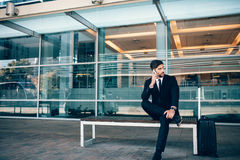 Handsome businessman sitting on bench at airport. Handsome businessman sitting on bench and talking on mobile phone with a suitcase at airport terminal. Business Royalty Free Stock Image