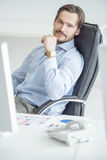 Handsome businessman sitting in chair in front of computer Stock Photography