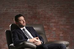 Handsome businessman sitting in comfortable armchair. On brick wall background Royalty Free Stock Photo