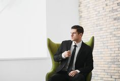 Handsome businessman sitting in comfortable armchair. Indoors Royalty Free Stock Photo