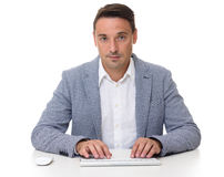 Handsome businessman sitting at desk, working on computer. Royalty Free Stock Images