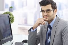 Handsome businessman sitting at desk Stock Photo