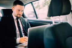 Handsome businessman sitting with laptop on the backseat of the car stock photos