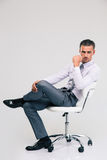 Handsome businessman sitting on office chair Stock Image