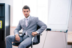 Handsome businessman sitting on the office chair. Handsome businessman in suit sitting on the office chair and looking at camera Royalty Free Stock Photos