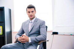 Handsome businessman sitting on the office chair Stock Images