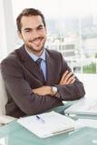 Handsome businessman sitting at office desk Stock Images