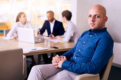 Handsome businessman sitting proudly in front of his business team. Aspirational businessman looking at camera with confident body langueage with his three Royalty Free Stock Photography