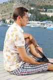 Handsome businessman sitting by the sea. With a laptop looking at the Bay City Royalty Free Stock Photos