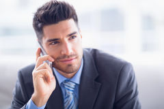 Handsome businessman sitting on sofa making a call Royalty Free Stock Photos