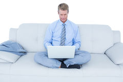 Handsome businessman sitting on sofa using his laptop Stock Images