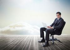 Handsome businessman sitting on a swivel chair and using his lap Stock Images