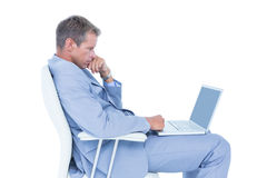 Handsome businessman sitting on a swivel chair and using his laptop Stock Photo