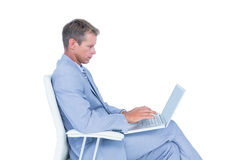 Handsome businessman sitting on a swivel chair and using his laptop Royalty Free Stock Photo