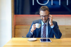 Handsome businessman sitting at table with coffee Stock Images