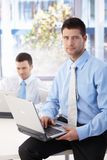 Handsome businessman sitting on top of desk Royalty Free Stock Photo