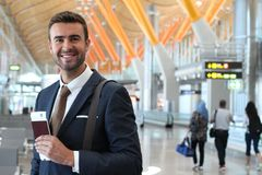 Handsome businessman smiling at the airport with space for copy.  Stock Images
