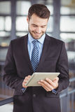 Handsome businessman smiling while looking at digital tablet Stock Image