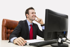 Handsome businessman smiling positively. In office while using his computer Stock Photography