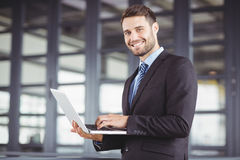 Handsome businessman smiling while using laptop. Portrait of handsome businessman smiling while using laptop in office Royalty Free Stock Photography
