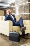 Handsome Businessman Speaking by Phone in Lobby Royalty Free Stock Photography