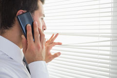 Handsome businessman spying through roller blind while phoning Stock Images