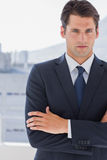 Handsome businessman standing with arms crossed Stock Images