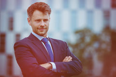 Handsome businessman standing with arms crossed. Outside office Royalty Free Stock Photography