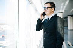 Handsome businessman standing next to the large windows of his top floor office, Stock Photos