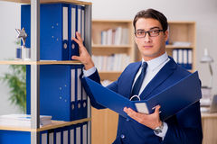 The handsome businessman standing next to shelf Stock Images