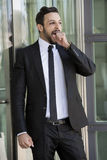 Handsome businessman standing outside and yawning Stock Photography