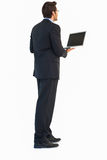 Handsome businessman standing using a laptop. On white background Stock Image