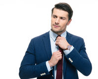 Handsome businessman straightening his tie Royalty Free Stock Images