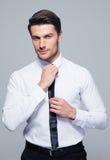 Handsome businessman straightening his tie Stock Image