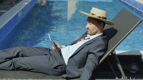Handsome businessman in straw hat uses tablet, drinks cocktail near the pool stock video footage
