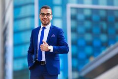 Handsome businessman in suit and eyeglasses standing near office stock photography