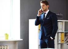 Handsome businessman in suit speaking on the phone Stock Images