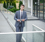 Handsome businessman in suit standing near office building. This handsome businessman in suit with laptop in his hands standing near office building Royalty Free Stock Image