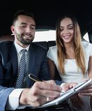 Beautiful business woman working with a client in the car. Handsome businessman in suit  is using a laptop and studying documents while driving on back seat in Royalty Free Stock Photos