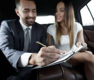 Beautiful business woman working with a client in the car. Handsome businessman in suit  is using a laptop and studying documents while driving on back seat in Royalty Free Stock Photo